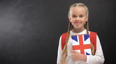 traductor : Smiling female pupil holding textbook with printed Great Britain flag, languages Archivo de Video