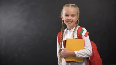 traductor : Happy schoolgirl holding books with Italy flag, ready to learn foreign language