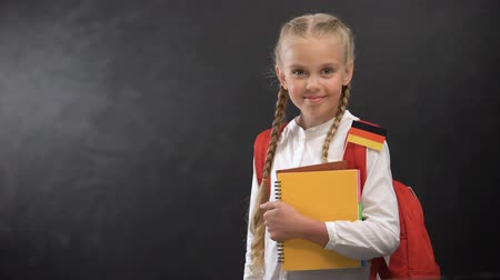 konu : Happy schoolgirl holding books with German flag, ready to learn foreign language