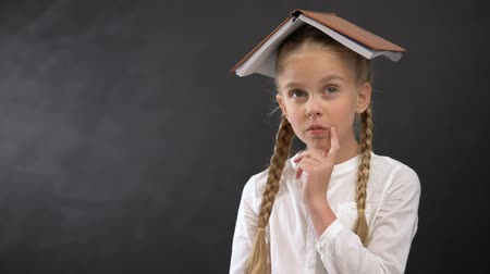 pokrývka hlavy : Funny schoolgirl with book on head planning homework schedule, education concept