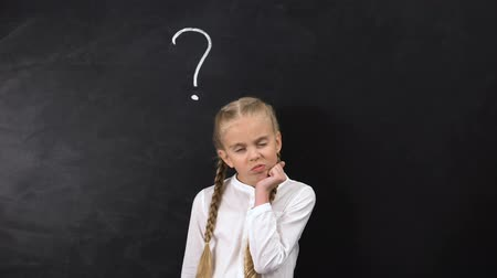 antwoord : Pupil thinking about answer, shrugging shoulders, question mark on blackboard