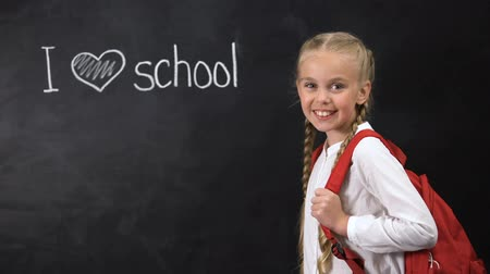 credo : I love school written on blackboard, cute girl standing near, primary education Filmati Stock