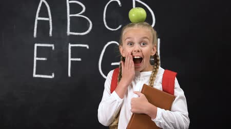 letter board : Pretty schoolgirl standing near blackboard with apple on head, brilliant idea