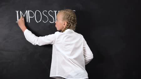 imposible : Smart girl standing near blackboard, crossing IM in word IMPOSSIBLE, motivation