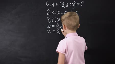 çözmek : Boy writing on chalkboard math equation, solving exercise, education reform Stok Video