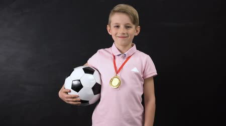 prominent : Boy with ball and medal standing near blackboard, football competition winner