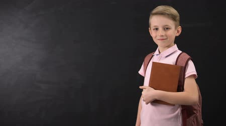 subject : Diligent schoolboy holding textbook, standing near blackboard, education system