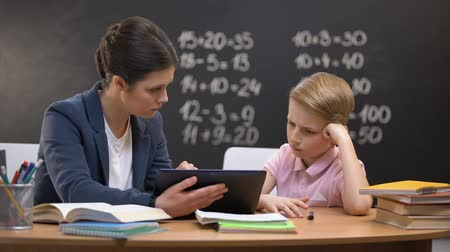 хмурый : Patient lady teacher explaining subject on tablet, schoolboy does not understand