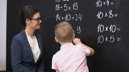 megoldani : Smart schoolboy solving math exercises on blackboard, teacher standing near Stock mozgókép