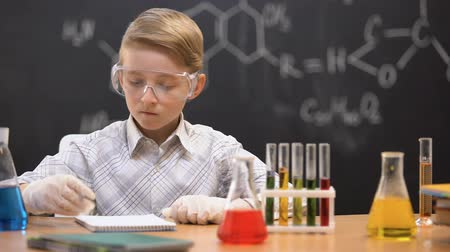 sediments : Schoolboy looking at sediment in flask and writing results, chemistry lesson
