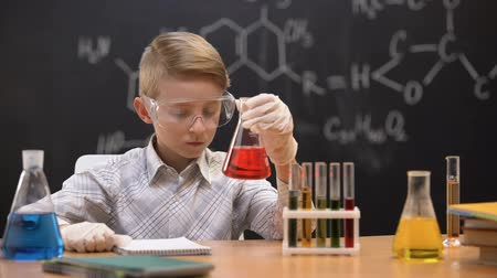 sediments : Schoolboy looking at red liquid in flask and scratching head, having no idea