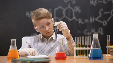 sediments : Schoolboy looking at chemical substance in test tube, chemistry lesson, hobby Stock Footage