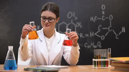 vzorec : Chemistry teacher comparing liquids in flasks and showing to camera, discovery