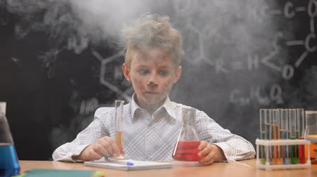 vzorec : Funny dirty schoolboy holding chemistry equipment, explosion during experiment