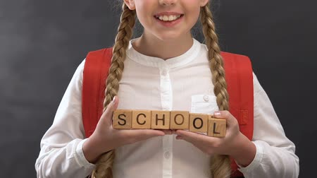 soutien scolaire : Nice little girl holding wooden cubes with school word against blackboard Vidéos Libres De Droits