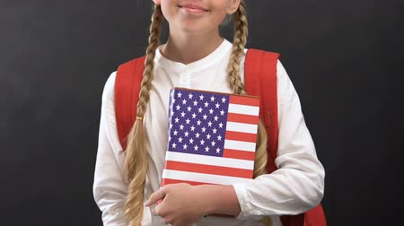 subject : Smiling schoolgirl holding book with USA flag, English language studying Stock Footage