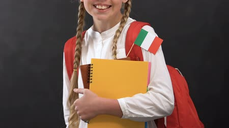 konu : Schoolgirl holding copy books with Italian flag and smiling at camera, language Stok Video