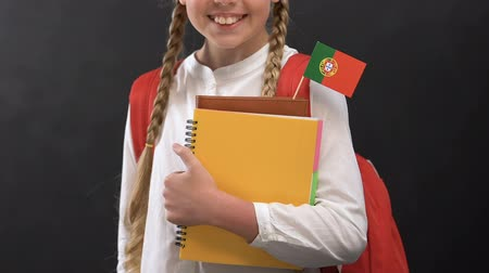 konu : Girl holding books with Portuguese flag and smiling at camera, language studying