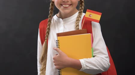 písanka : Little girl holding books with Spanish flag and smiling at camera, language Dostupné videozáznamy
