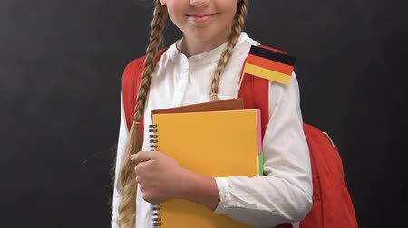 písanka : Little girl with books and German flag smiling at camera, language studying