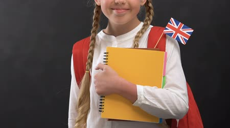 konu : Cheerful girl with books and British flag smiling at camera, language studying