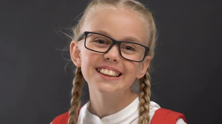 compito : Happy schoolgirl in eyeglasses smiling at camera against blackboard, education