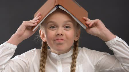 remember : Pretty schoolgirl with book on head laughing and fooling around, childish mood Stock Footage