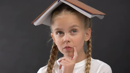 запомнить : Funny schoolgirl thinking with book on head, full of ideas, educational process Стоковые видеозаписи