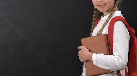 subject : Schoolgirl with book and rucksack pointing finger at blackboard, template
