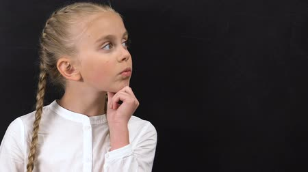 warkocz : Thoughtful little girl touching chin and looking to side, template for text