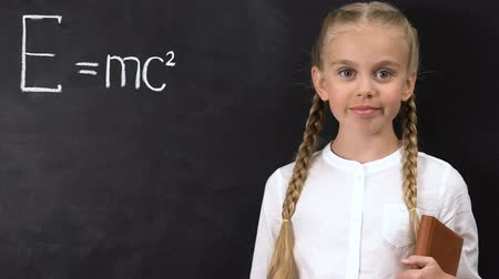 subject : Smart schoolgirl pointing chalk into physical formula written on blackboard Stock Footage