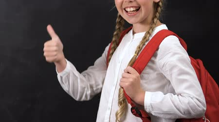 konu : Smiling schoolgirl with rucksack showing thumbs up, courses, template for text