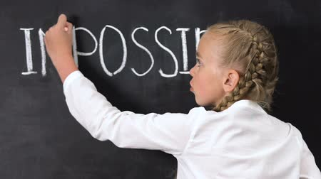 ösztönző : Girl correcting word impossible to possible written on blackboard, motivation