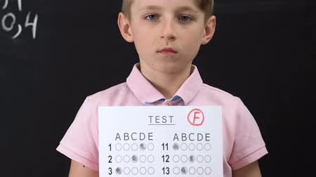 notas : Upset schoolboy holding test with failed result, low grade, studying problems