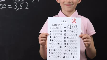 klasa : Happy schoolboy holding test with good result, high grade, honor student Wideo