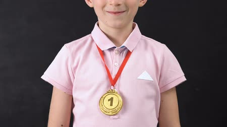 primer lugar : Smiling schoolboy with first place medal looking at camera, diligent student Archivo de Video