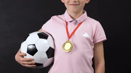 medaille : Cheerful little boy with golden medal on neck holding soccer ball, competition Stockvideo