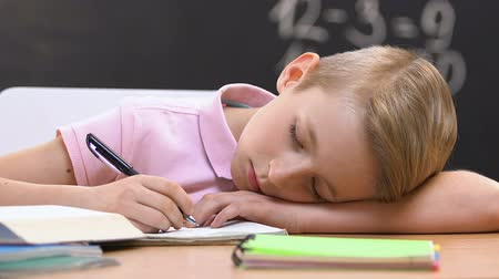task : Tired schoolboy sleeping on desk at lesson, exhausted education, overwork Stock Footage