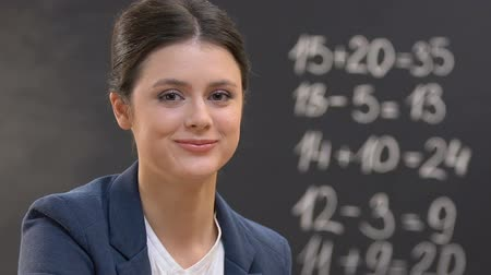 директор : Young teacher looking at camera, mathematics equations on blackboard, close-up