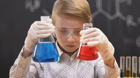 produtos químicos : Little scientist comparing flasks with blue and red liquids, experiment result