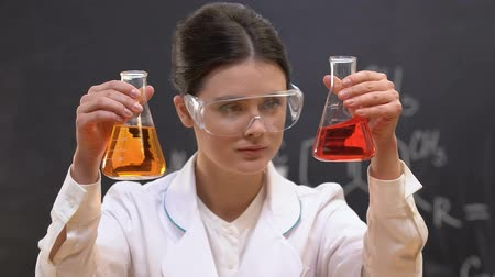 banka : Young female scientist comparing red and yellow liquids in flasks, laboratory