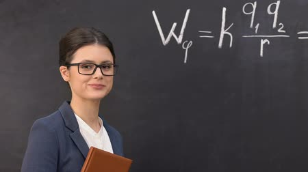 subject : Smiling teacher looking at camera, physical formula written on blackboard