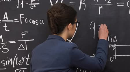 képviselő : Female teacher writing physical formulas on blackboard, exact science studying Stock mozgókép