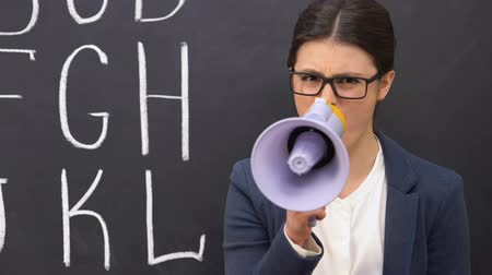 мегафон : Nervous female teacher shouting in megaphone against blackboard background Стоковые видеозаписи