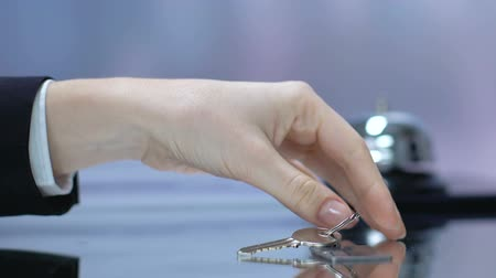 register : Woman taking key with hotel keychain at reception desk, luxury spa resort Stock Footage