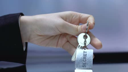 vazamento : Secret word on keychain, woman taking key at reception desk, confidentiality