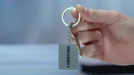 political intervention : Business partner sharing lobbying keychain, promotion of initiatives in politics Stock Footage