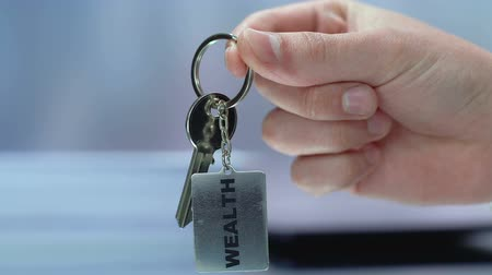 self promotion : Wealth word on keychain in businessman hand, successful and reach life, close-up