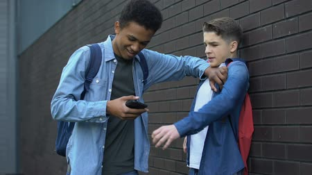 tehetetlen : Black teenager taking away phone from boy, making fun of social media account Stock mozgókép