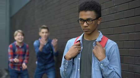 abused : Cruel teenagers teasing african american boy, immigrant newcomer facing racism